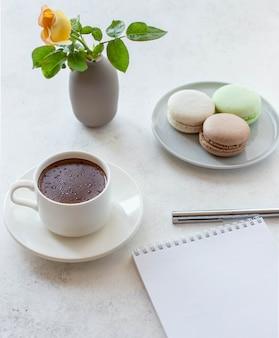 Tazza di cioccolata calda con fiori macarons e blocco note su uno sfondo bianco