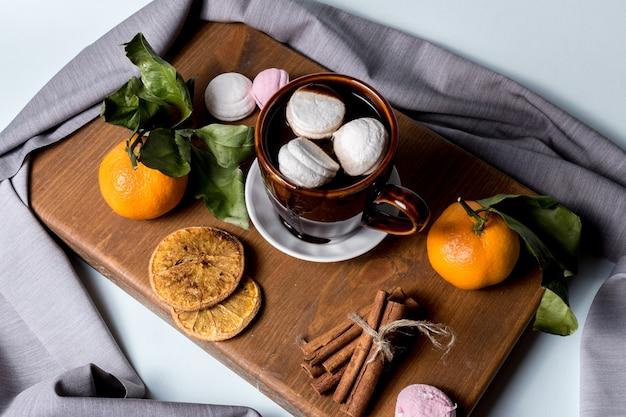 Tazza di cioccolata calda con marshmallow, cannella, frutta mandarino, frutta candita all'arancia.