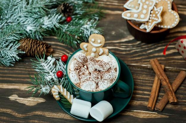 Tazza di cioccolata calda con marshmallow, durante le vacanze invernali di capodanno, biscotti, albero di natale su uno sfondo di legno