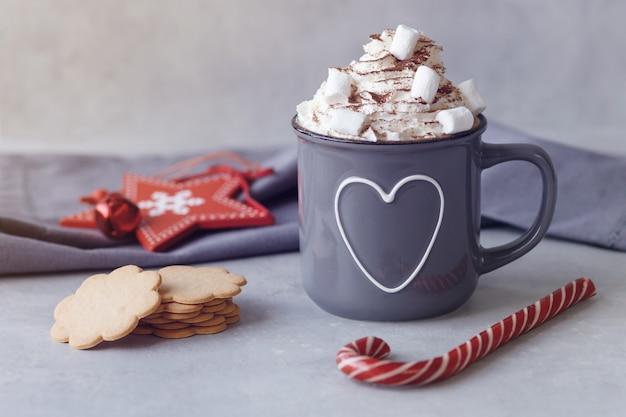 Tazza di cioccolata calda con panna montata, caramelle gommosa e molle e lecca-lecca rossa, stella rossa, biscotti su un fondo grigio. bevanda calda d'inverno