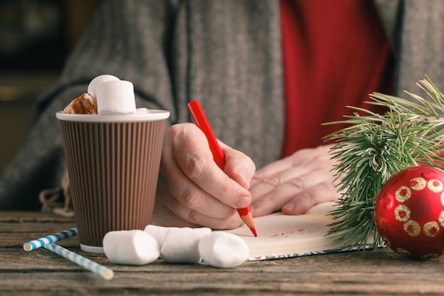 Tazza di cioccolata calda e libro con i vetri sulla tavola di legno