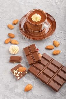 Tazza di cioccolata calda e pezzi di cioccolato al latte con mandorle