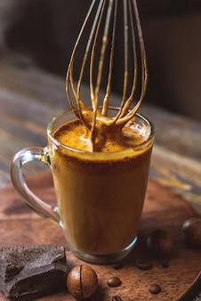 Tazza di delizioso caffè freddo dalgona e frusta da cucina con mousse montata
