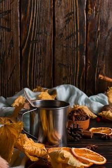 Tazza di ferro con caffè nero, spezie, arance secche, su uno sfondo di una sciarpa, foglie secche su un tavolo di legno. mood autunnale, una bevanda calda. copyspace.