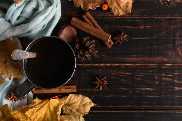 Tazza di ferro con caffè nero, spezie, su uno sfondo di una sciarpa, foglie secche su un tavolo di legno. mood autunnale, una bevanda calda. copyspace.