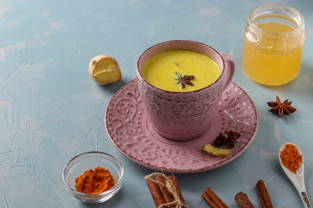 Tazza di latte ayurvedico di latte di curcuma dorata con polvere di curcuma, cannella, zenzero e anice stellato su superficie blu chiaro, spazio di copia