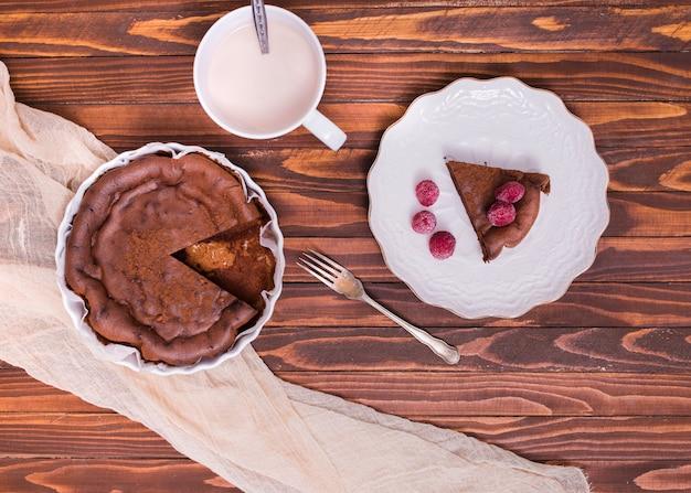 Tazza di latte; fetta di torta e lampone sul piatto in ceramica bianca sopra la superficie in legno