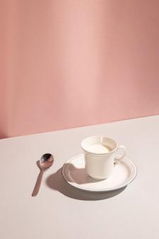 Tazza di latte fresco con il cucchiaio sopra lo scrittorio bianco