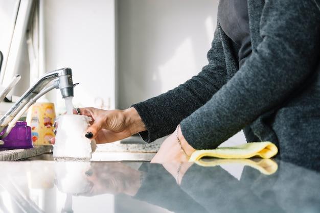 Tazza di lavaggio della mano della donna nel lavandino