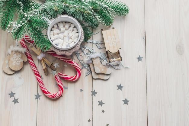 Tazza di marshmallow e bastoncini di zucchero circondati da decorazioni natalizie sul tavolo