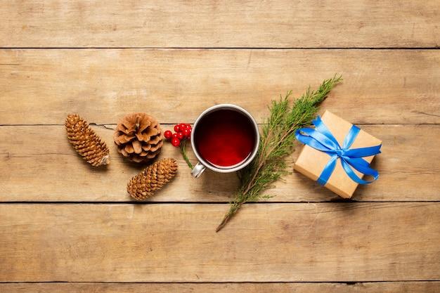 Tazza di metallo con tè caldo, coni, un rametto di un albero di natale e un regalo su un fondo di legno. un umore invernale, natale, vacanze invernali. vista piana, vista dall'alto