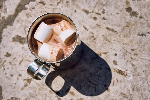 Tazza di metallo turistico di cacao con marshmallow su una pietra