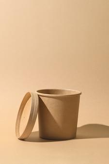 Tazza di minestra di carta artigianale con ombra su sfondo di carta marrone. contenitore vuoto. pacchetto ecologico individuale. rifiuti zero.