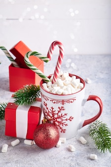 Tazza di natale con caramelle gommosa e molle al cacao, confezione regalo e caramelle. rami di abete, confezione regalo di natale su sfondo chiaro copia spazio