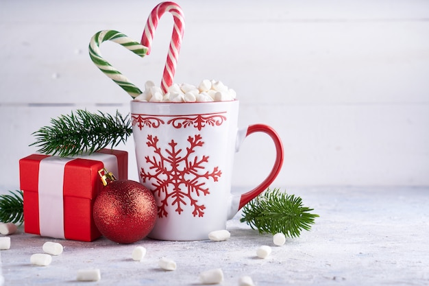 Tazza di natale con caramelle gommosa e molle al cacao e zucchero. rami di abete, confezione regalo di natale su sfondo chiaro copia spazio.