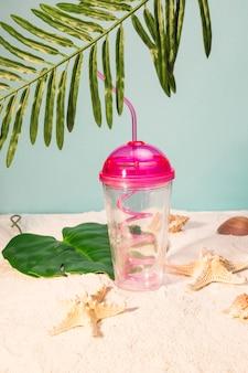Tazza di plastica con paglia sulla spiaggia