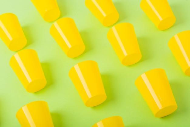 Tazza di plastica gialla su sfondo verde