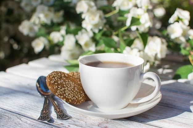 Tazza di porcellana bianca con tè e due biscotti di farina d'avena con semi di sesamo su un tavolo di legno sullo sfondo di gelsomino in fiore.