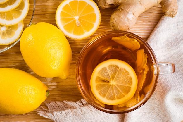 Tazza di tè al limone e fette di zenzero e limone su un piatto su un tavolo di legno