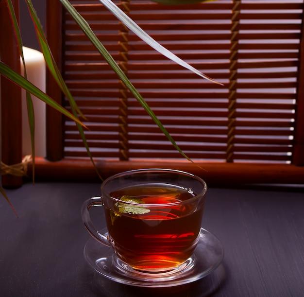 Tazza di tè alla menta su un fondo di legno.