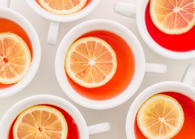 Tazza di tè allo zenzero con fetta di limone su sfondo bianco