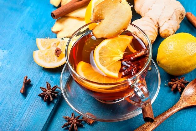 Tazza di tè allo zenzero con limone e miele su blu scuro,