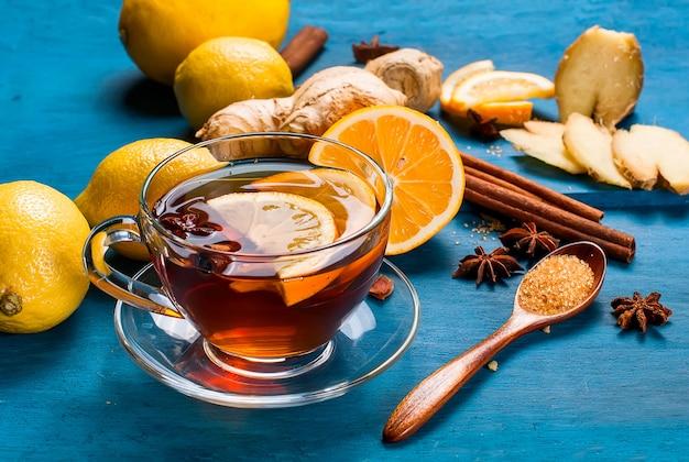 Tazza di tè allo zenzero con limone e miele su sfondo blu scuro,