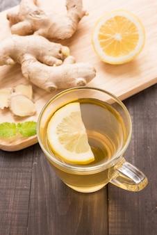 Tazza di tè allo zenzero con limone sul tavolo di legno