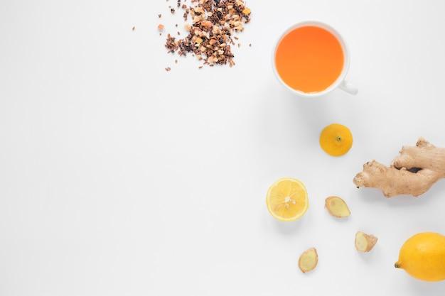 Tazza di tè allo zenzero; limone; erbe e miele su sfondo bianco