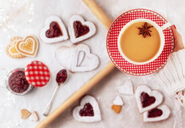 Tazza di tè aromatizzato chai ottenuto dalla preparazione di tè nero con spezie ed erbe aromatiche con biscotti fatti in casa a forma di cuore con marmellata di lamponi