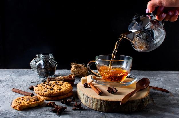 Tazza di tè, biscotti, cannella, anice su sfondo scuro