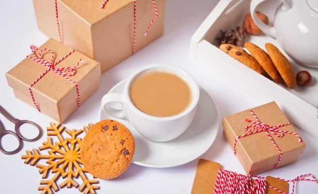 Tazza di tè, biscotti fatti in casa, scatole regalo di natale e decorazioni natalizie sul bianco.