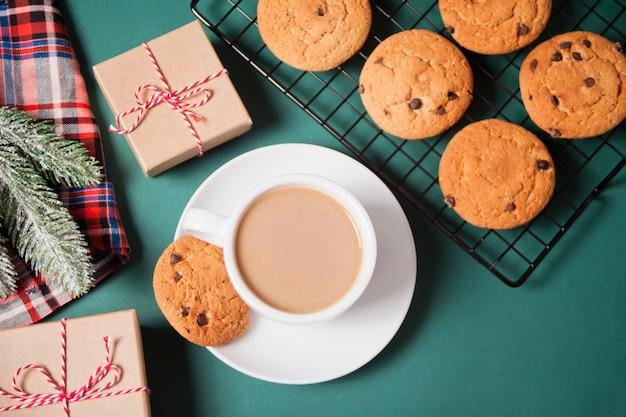 Tazza di tè, biscotti fatti in casa, scatole regalo di natale e decorazioni natalizie
