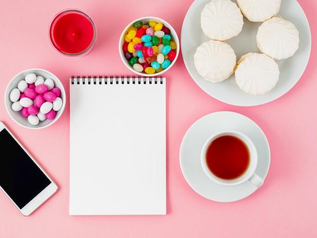Tazza di tè, blocco note, cellulare e piatti di diversi dolci - marshmallow, lecca lecca