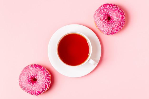 Tazza di tè con ciambelle su uno sfondo rosa pastello