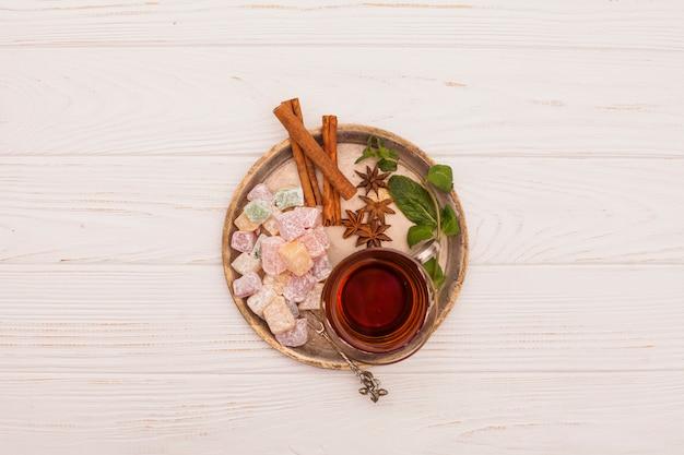 Tazza di tè con delizia turca e cannella sul piatto