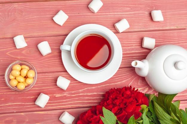 Tazza di tè con dolci e fiori sul tavolo di legno