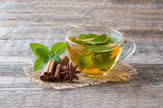 Tazza di tè con foglie di menta fresca e anice di cannella su legno