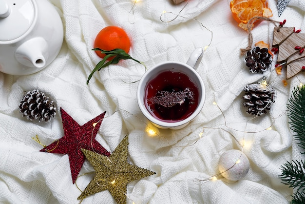 Tazza di tè con i mandarini ed i maglioni sul fondo del letto
