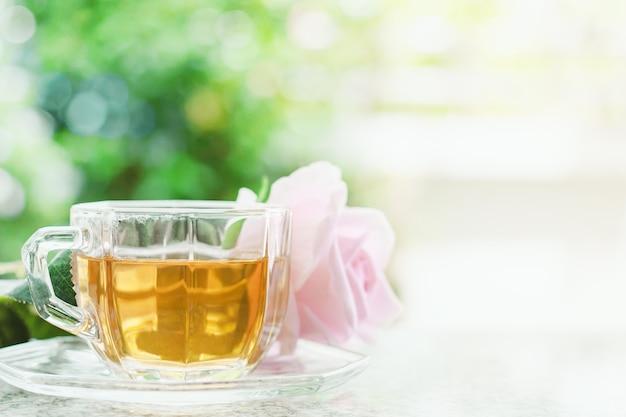 Tazza di tè con il fiore dolce della rosa di rosa contro fondo verde naturale vago