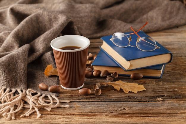 Tazza di tè con il vecchio libro, foglie di autunno sul tavolo di legno.