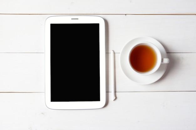 Tazza di tè con la compressa e la penna sulla tavola di legno bianca.