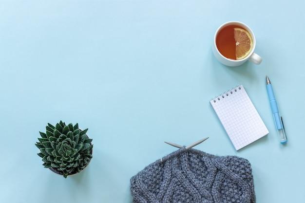Tazza di tè con limone, blocco note, penna. vaso con succulente e tessuto sui ferri da maglia