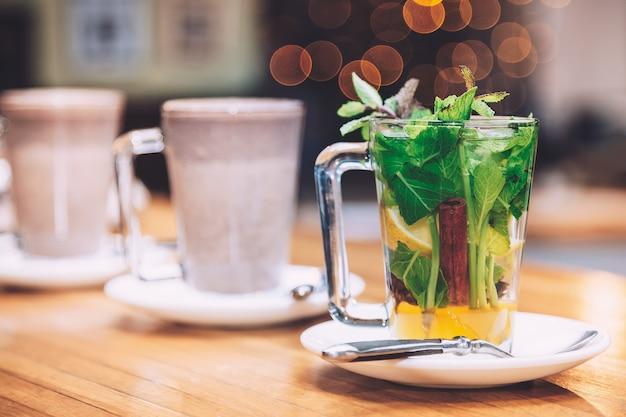 Tazza di tè con menta, cannella e limone del piatto bianco