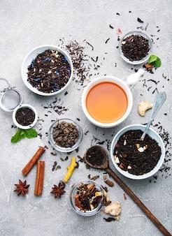 Tazza di tè con tè aromatico secco in ciotole