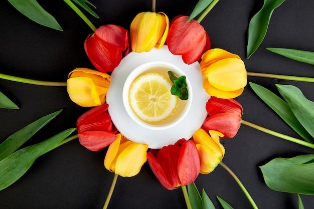 Tazza di tè con tulipano rosso e giallo intorno.