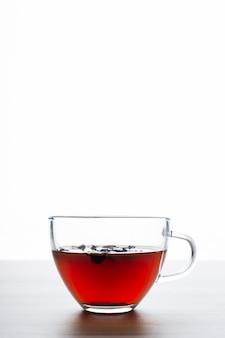 Tazza di tè con uno sfondo bianco su un tavolo di legno