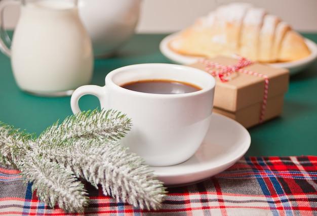 Tazza di tè, cornetto fatto in casa, confezione regalo di natale e ramo di pino di natale sullo sfondo verde