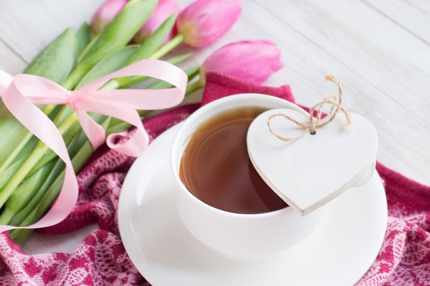 Tazza di tè, cuore in legno e tulipani