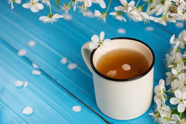 Tazza di tè della primavera, fiore di ciliegia su fondo di legno blu